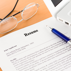 Resume with glasses and pen laid on top