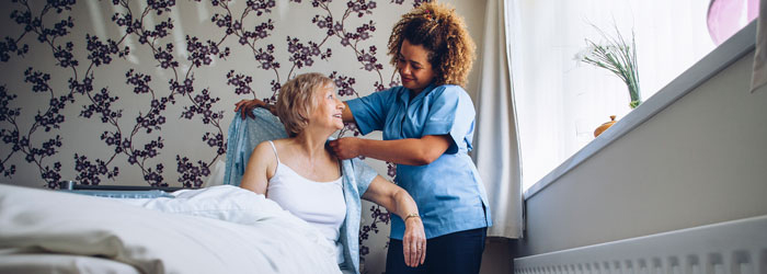 Hospice aide helping patient get dressed