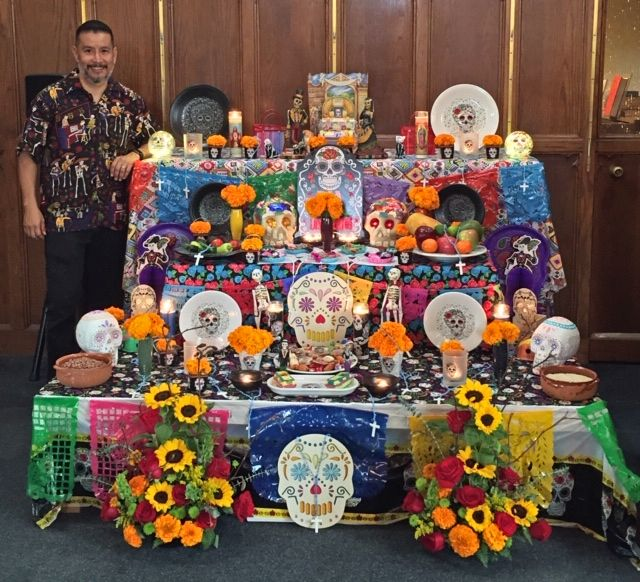 Alex next to an altar created for Dia de los Muertos