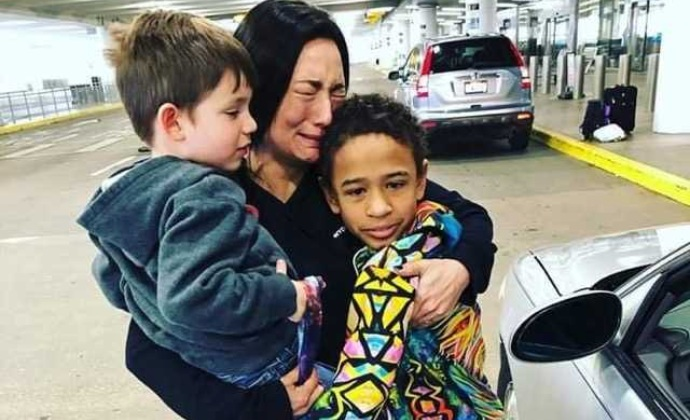 Alisa cries as she hugs her children at the airport en route to NYC