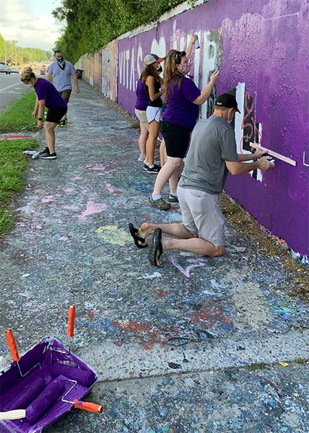The team first paints a base coat of VITAS purple over the expanse of wall