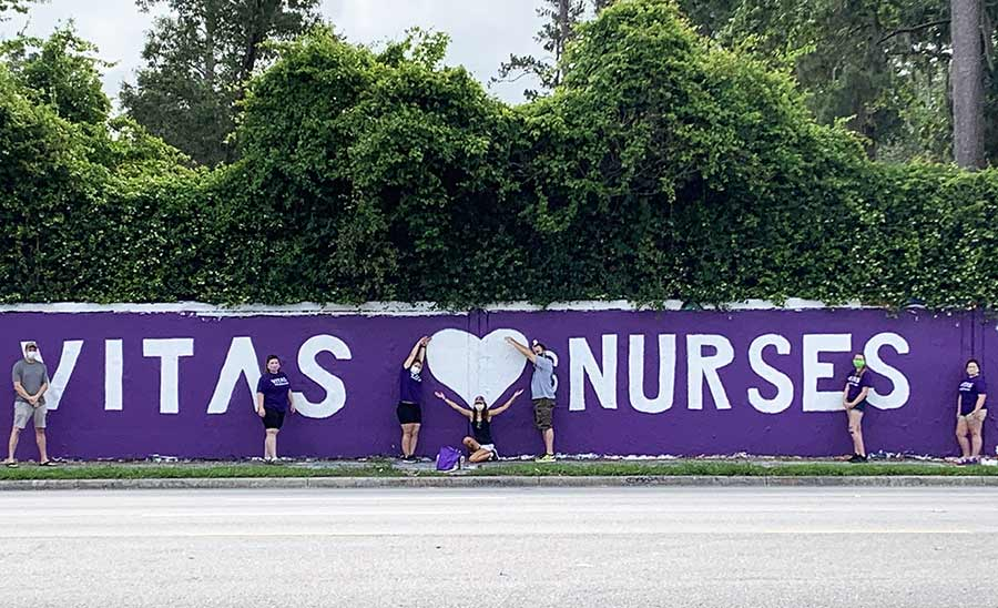 The artists pose with the completed mural, which has a purple background and white letters