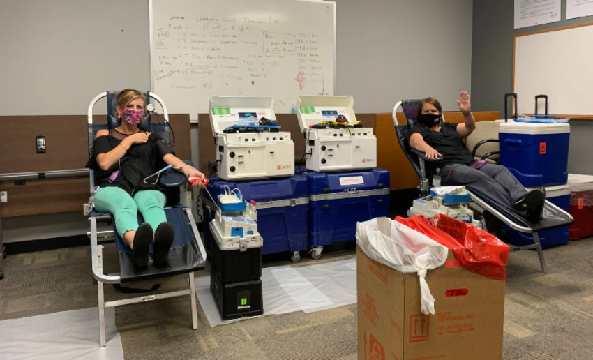 Two VITAS employees wave hello as they donate blood at the program office