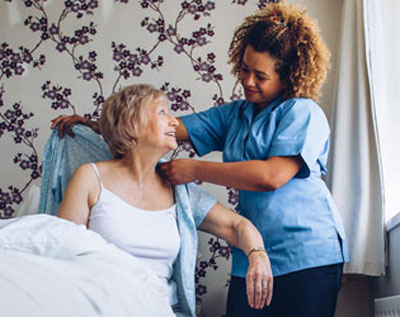 A hospice aide helps a patient