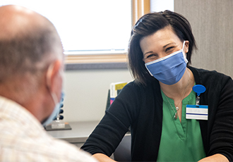 A VITAS team member talks with a patient's family member