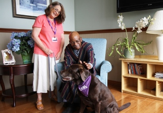 A VITAS PawPals volunteer and her dog visit with a patient