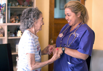 A nurse holds hands with a patient as they share a smile