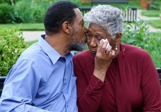 Un hombre consuela a su esposa sentados en la banca de un parque