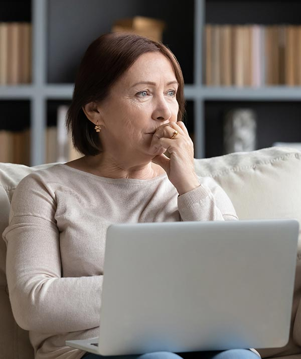 A man looks into the distance as she sits on a sofa with a laptop on her lap