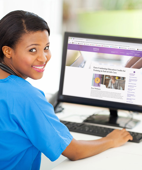 A nurse uses a desktop computer to register for a VITAS webinar