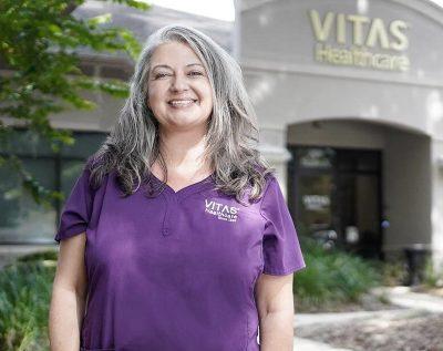 Isang nurse ng VITAS na nakangiti sa labas ng opisina ng VITAS