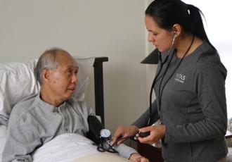 一位在病人家中的VITAS護士正在使用聽診器檢查坐在床上的病人