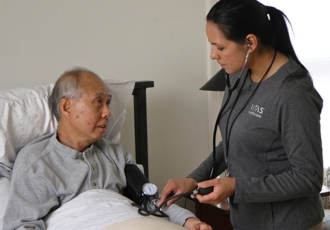 A VITAS nurse uses a stethoscope to check on a patient as he sits up in bed at home