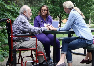 A VITAS care team member sits at an outdoor picnic table with a patient and his daughter