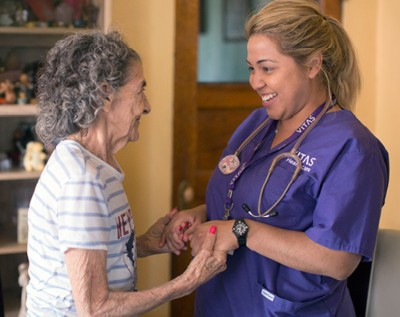 A VITAS nurse and patient hold hands and smile