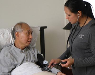 Một thành viên nhóm của VITAS đang đo huyết áp cho bệnh nhân khi ông này đang nằm trên giường