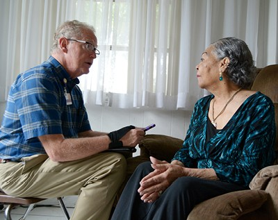 A VITAS team member talks with a patient in her home