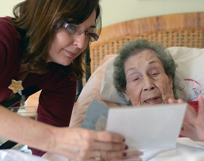 A VITAS team member helps a patient review documents as she lies in bed