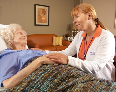 A VITAS nurse comforts a patient in a bed