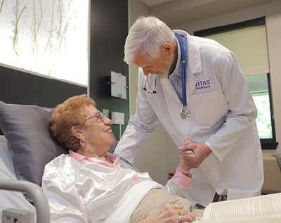 A physician talks with a patient in a hospital bed