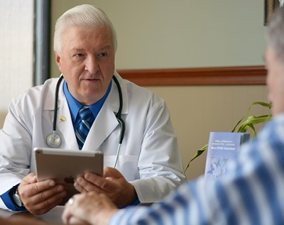 A physician talks with a patient at his desk