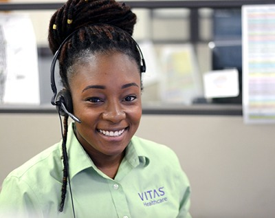 A smiling VITAS employee at a desk in their office