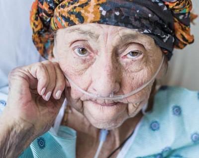 Una mujer se sienta junto a la cama de su esposo mientras él descansa con oxígenosuplementario