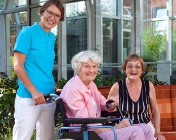 Một tình nguyện viên đang giúp một bệnh nhân ngồi trên xe lăn