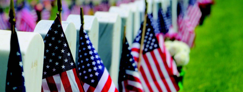 Isang hanay ng mga American flag na nakalagay sa mga puntod