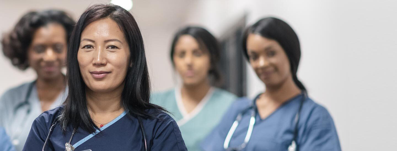 Nakangiti ang isang nurse habang tinutulungan niya ang isang pasyente