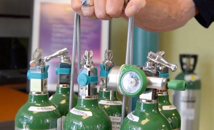 Lalaking may hawak na rack ng mga oxygen tank