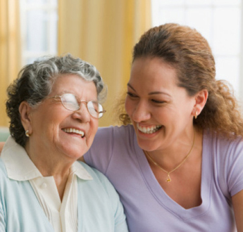 An older woman and a younger woman smile at each other