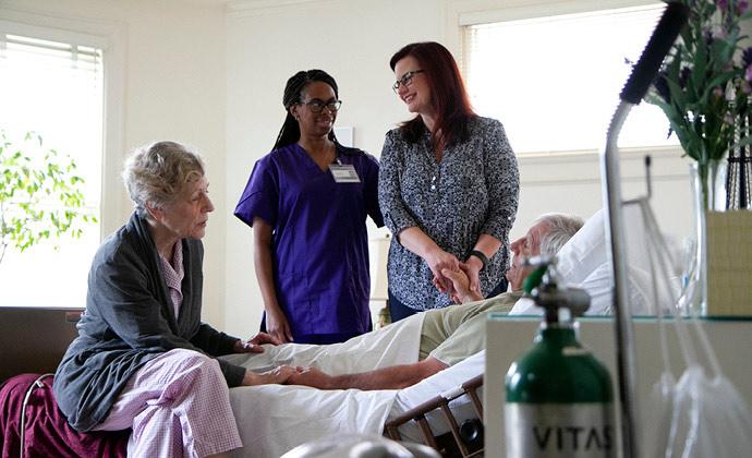 Napapaligiranang isang lalaking nakahiga sa kamang kanyang asawa, anak, at nurse ng VITAS hospice