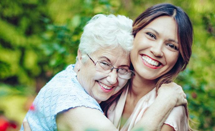 Một người phụ nữ lớn tuổi bên cạnh người chăm sóc trẻ tuổi