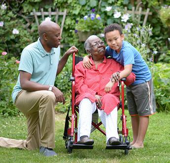女士在戶外坐在輪椅上休息,她的孫子抱著她