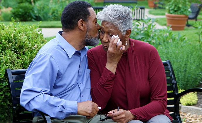 一對夫妻坐在公園的長凳子上,其中先生正在安慰太太