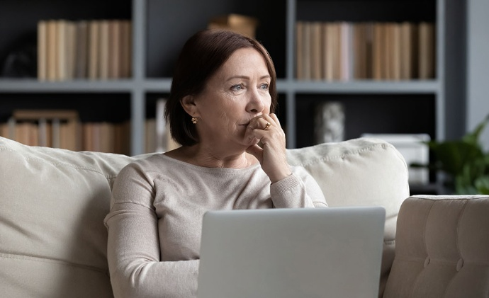 A woman sits on a sofa with a laptop, looking into the distance