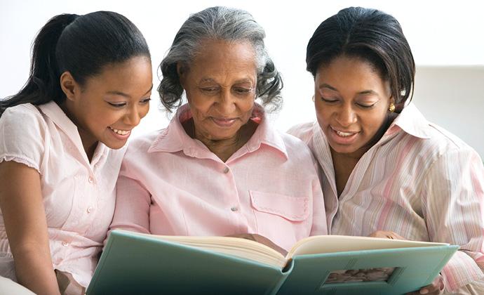 Una mujer mira un álbum de fotos familiares junto a sus dos nietas