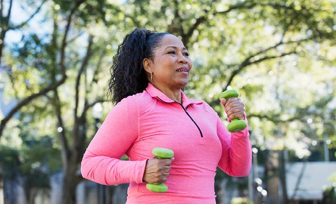 Isang babaeng nagpa-power walk sa labas habang may hawak na maliit na weight sa parehong kamay