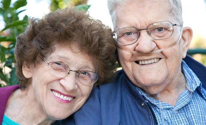 Un hombre con tubos de oxígeno sonríe junto a su esposa