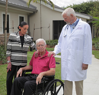 A man in a wheelchair receives help from his wife and his physician