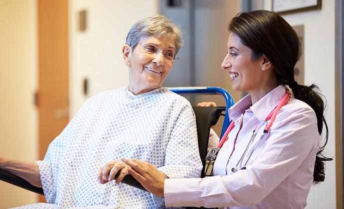 Una mujer en silla de ruedas sonríe a su médica