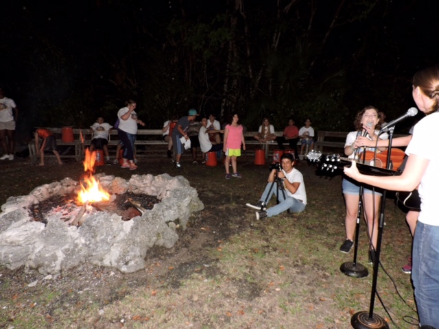 Camp VITAS members singing around a fire