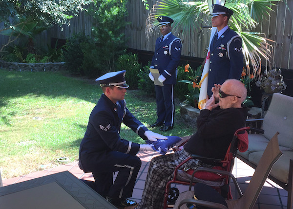 The Eglin Air Force Base Honor Guard presents 100-year old WWII veteran Herbert Clippinger with his honorary flag.