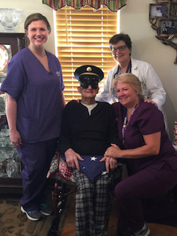 100 year old veteran sits surrounded by staff with his honorary flag