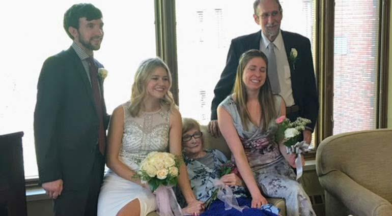 Wedding participants smiling with hospice patient