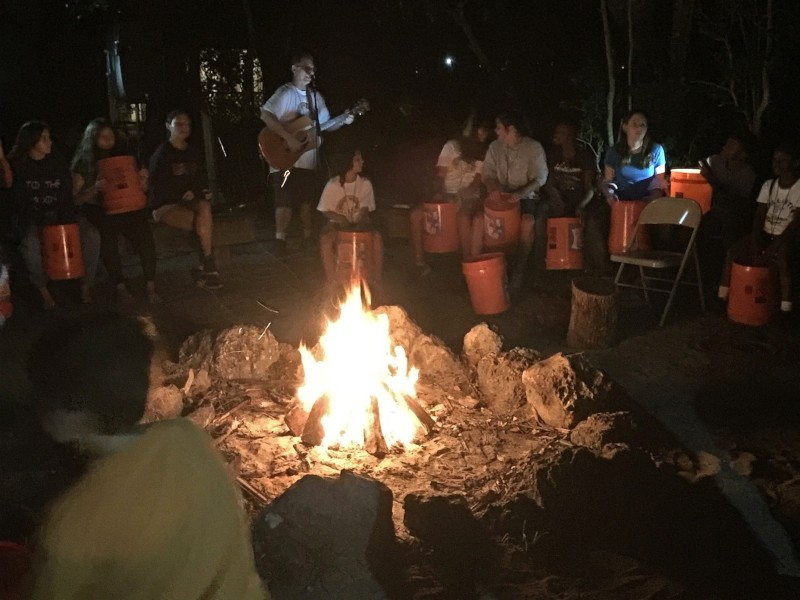 Tom leads the group in songs around the campfire at night