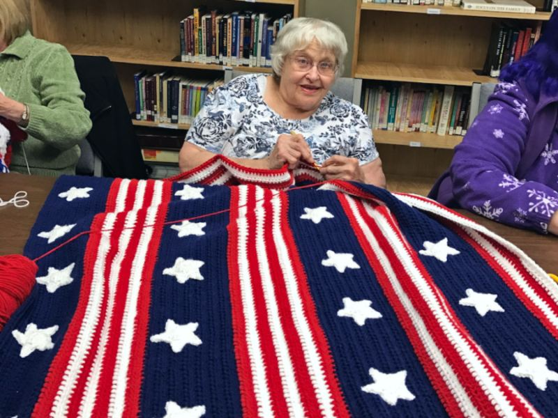 Volunteer Jane Polly works on a star-spangled blanket