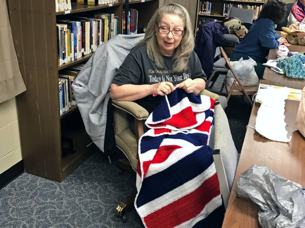 Volunteer Kanda Redding crochets a red, white and blue blanket