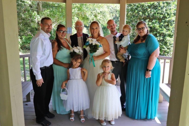 The wedding party gathered under a gazebo for pictures